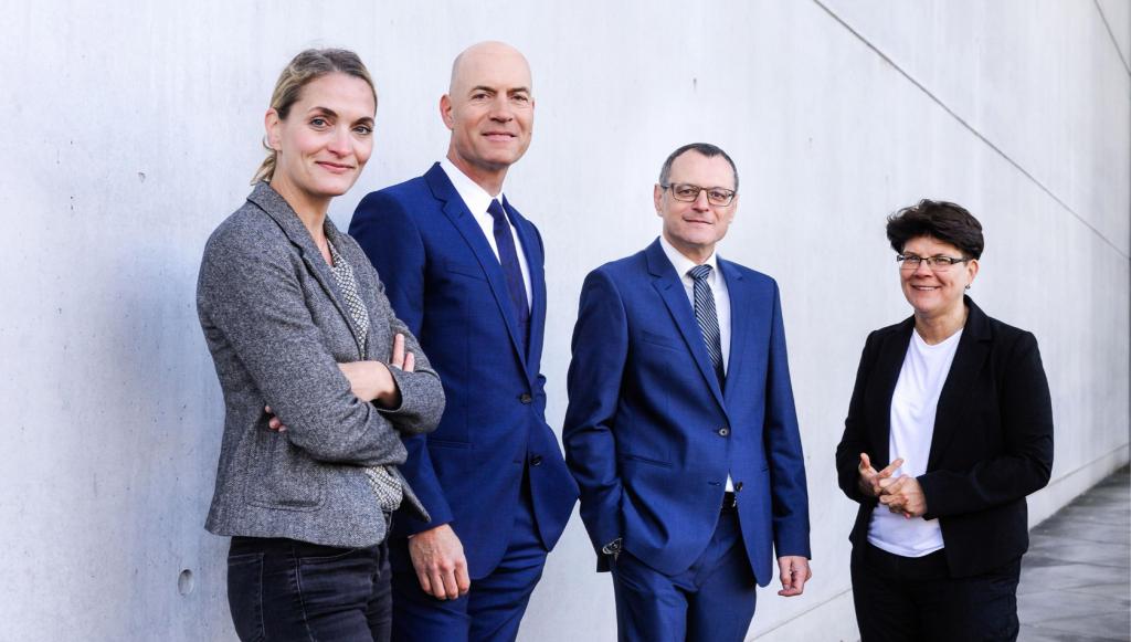 Ein Bild unserer vier Anwälte. Von links nach rechts Jutta Engels, Florian Haußleiter, Dieter Birkeneder und Karin Brandenburger. Sie stehen in Arbeitskleidung mit zuversichtlichem Lächeln vor einer grauen Mauer.