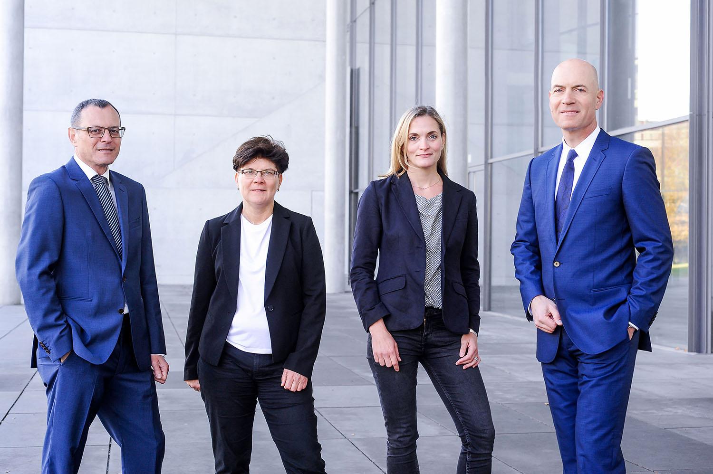 Ein Bild unserer vier Anwälte. Von links nach rechts Dieter Birkeneder, Karin Brandenburger, Jutta Engels und Florian Haußleiter. Sie stehen in Arbeitskleidung mit zuversichtlichem Lächeln vor einem grauen Gebäude mit Glasfassade..